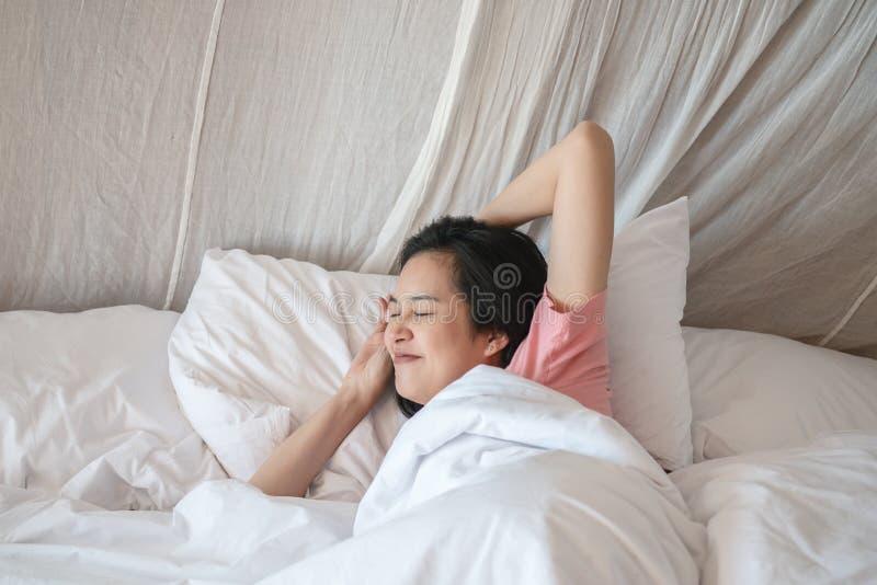 Femme asiatique de plan rapproché étirée après s'être réveillé pendant le matin photographie stock
