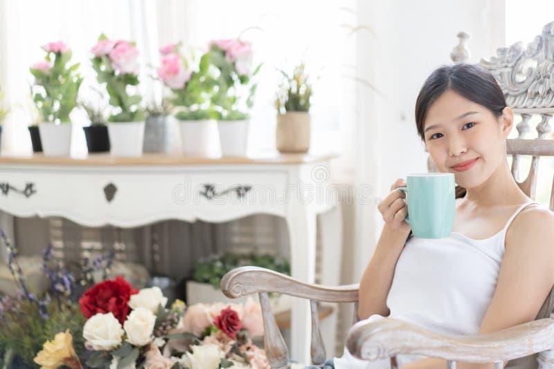 Femme asiatique de portrait détendant sur la chaise en bois avec du café à la maison photos libres de droits