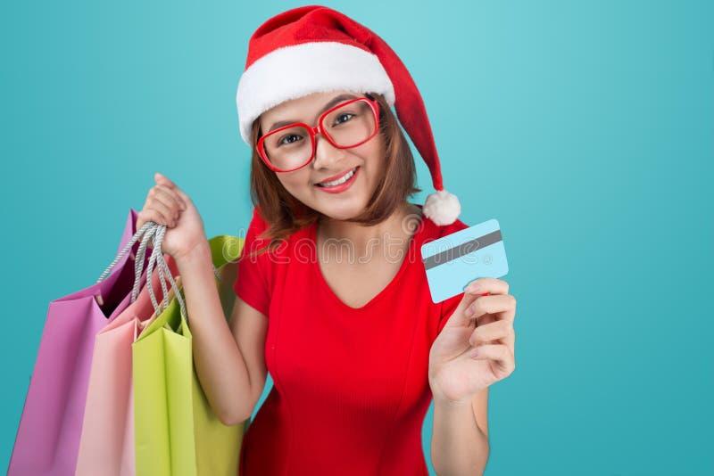 Femme asiatique de Santa tenant les paniers et la carte de crédit contre photo stock