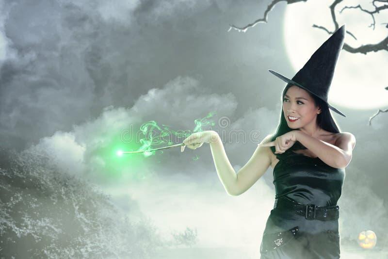 Femme asiatique de sorcière à l'aide de la baguette magique avec l'éclat magique image stock
