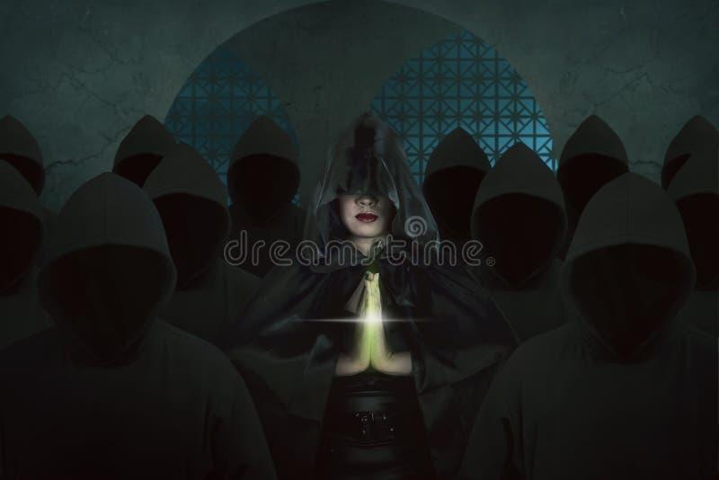 Femme asiatique de sorcière à l'intérieur de vieux château dans la prière de chambre noire photos libres de droits