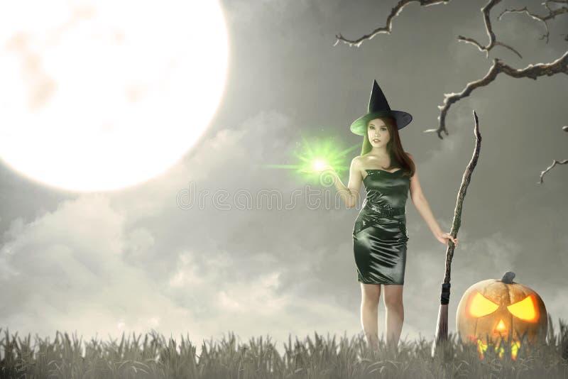 Femme asiatique de sorcière avec l'éclat magique sur sa main et balai images libres de droits