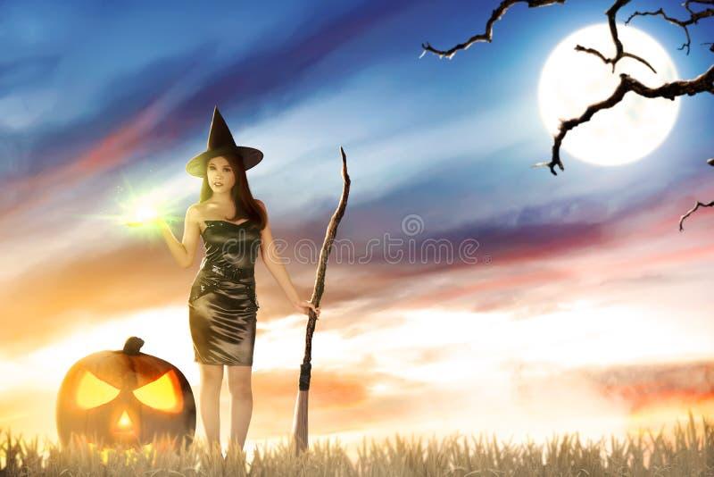 Femme asiatique de sorcière avec l'éclat magique sur sa main et balai images stock