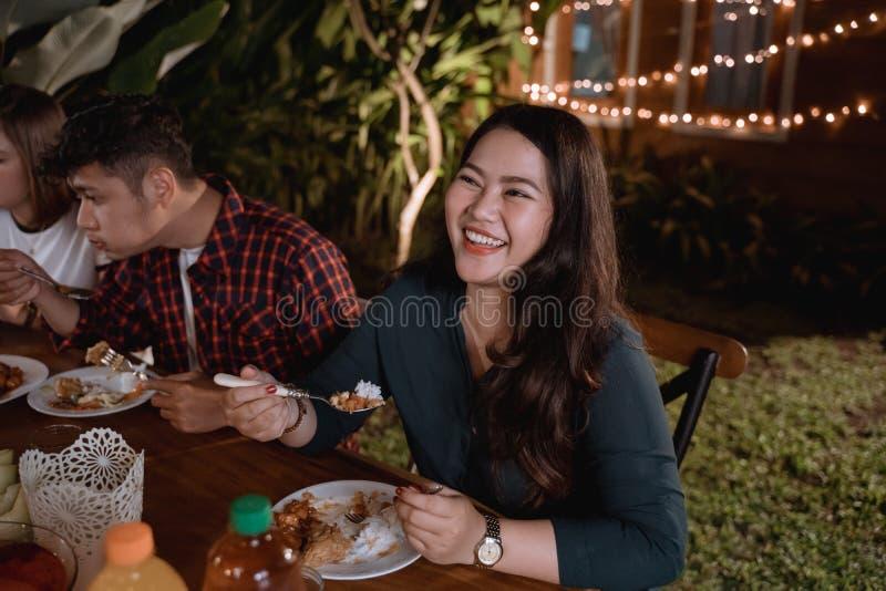 Femme asiatique de sourire appréciant leur dîner de jardin image stock