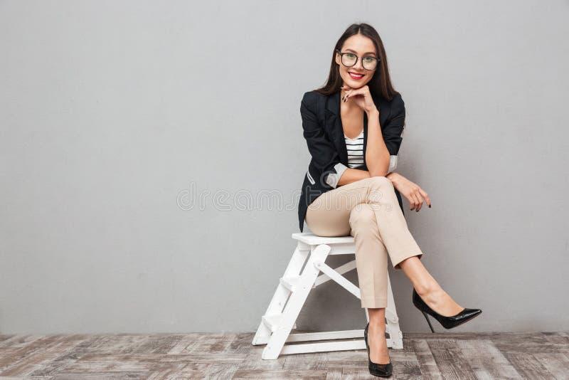 Femme asiatique de sourire d'affaires dans des lunettes se reposant sur la chaise photos stock