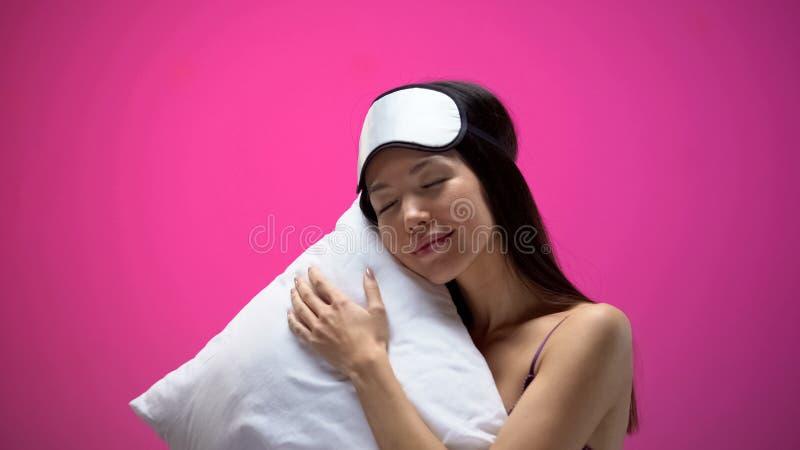 Femme asiatique de sourire dormant dans le bandeau sur l'oreiller confortable mol, toile images libres de droits