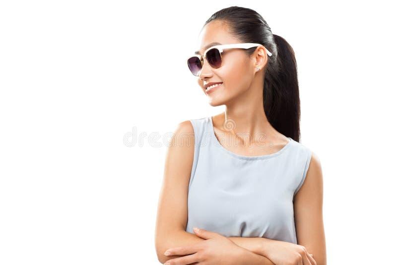 Femme asiatique de sourire de jeunes dans des lunettes de soleil photographie stock libre de droits
