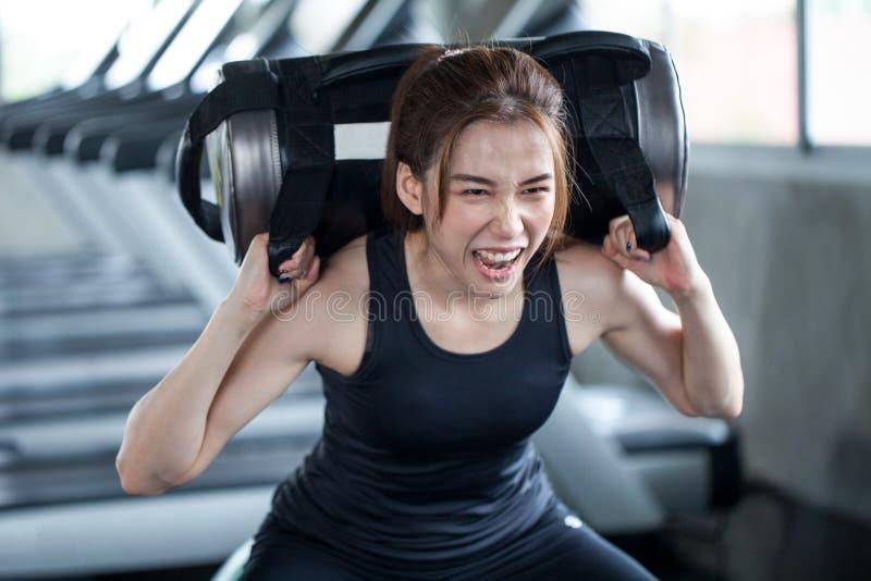 femme asiatique de sport dans la posture accroupie d'exercice de vêtements de sport avec avec le trainin image stock