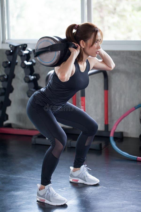 femme asiatique de sport dans la posture accroupie d'exercice de vêtements de sport avec avec le trainin photographie stock libre de droits