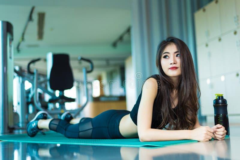 Femme asiatique de sport marchant ou courant sur l'équipement de tapis roulant dans f image libre de droits
