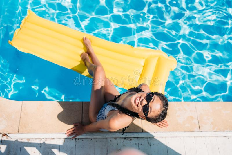Femme asiatique de vue supérieure se reposant près de la piscine photo libre de droits