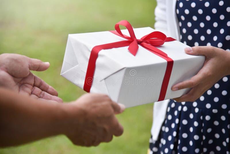 Femme asiatique donnant un boîte-cadeau blanc à l'homme plus âgé photographie stock libre de droits