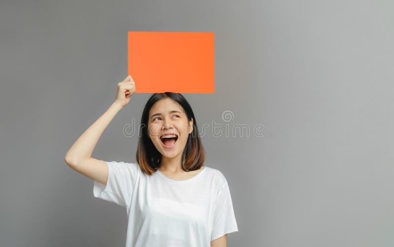 Femme asiatique du sourire heureux tenant une affiche orange vide sur le fond gris image libre de droits