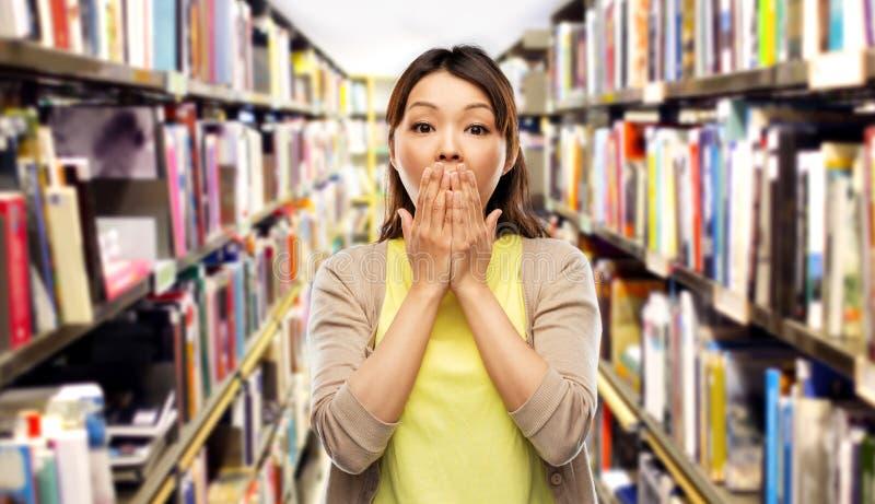 Femme asiatique effrayée à la bibliothèque photographie stock libre de droits