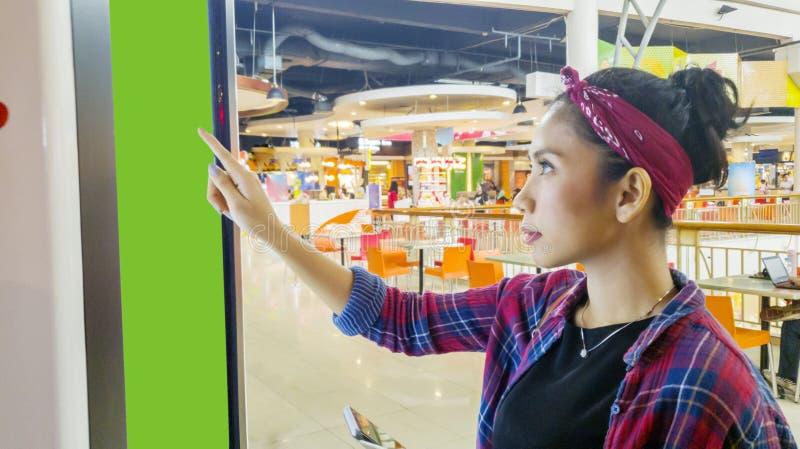 Femme asiatique employant un Kiosque de libre-service dans le mail photos stock