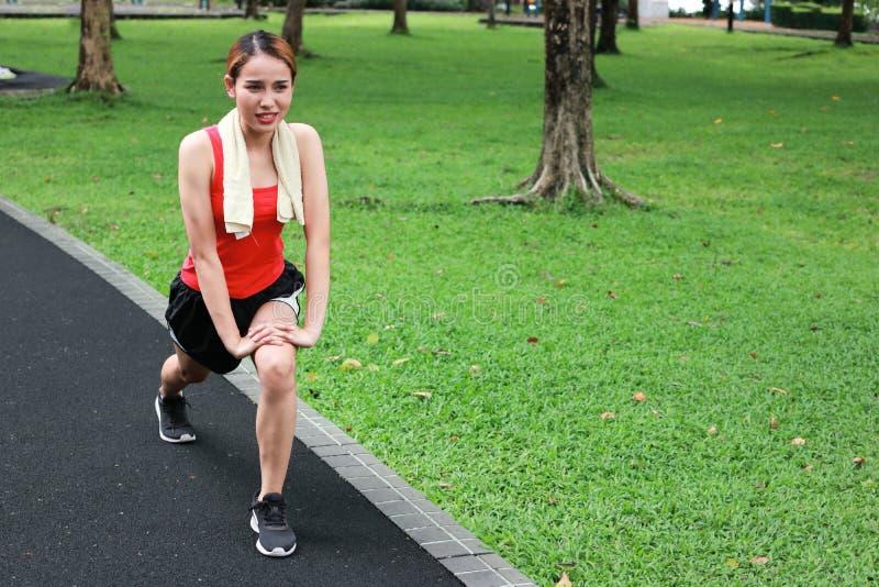 Femme asiatique en bonne santé étirant ses jambes avant course en parc Concept de forme physique et d'exercice photo libre de droits