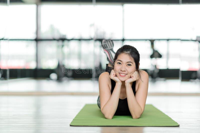 Femme asiatique en bonne santé détendant sur le tapis d'exercice photos stock