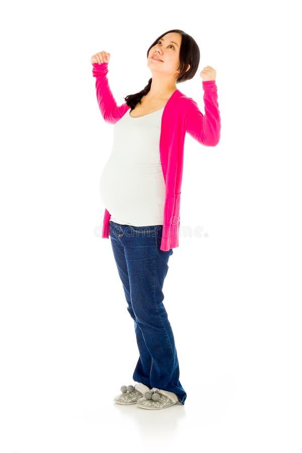 Femme asiatique enceinte d'isolement sur la victoire blanche images stock