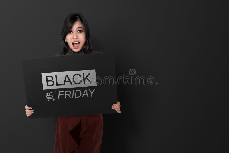 Femme asiatique enthousiaste tenant la bannière avec des announcemen de Black Friday images stock
