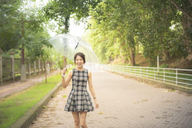 Femme asiatique heureuse, étudiant de collage de robe d'université dans la promenade d'umbella de prise de main de tenue décontra photo libre de droits