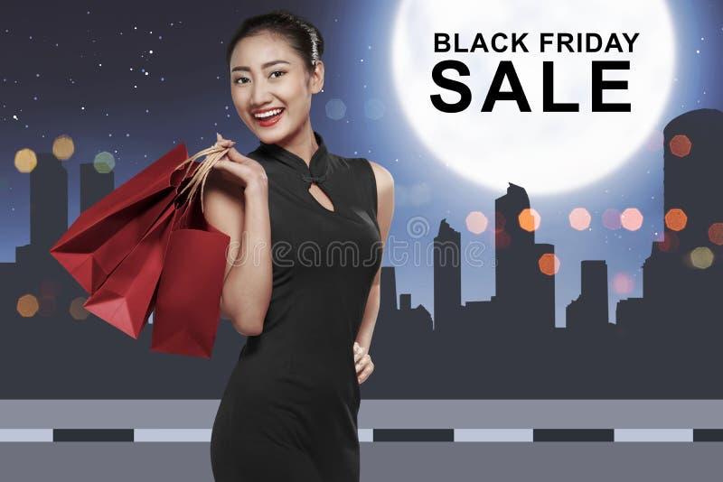 Femme asiatique heureuse avec des paniers avec le message de Black Friday image stock