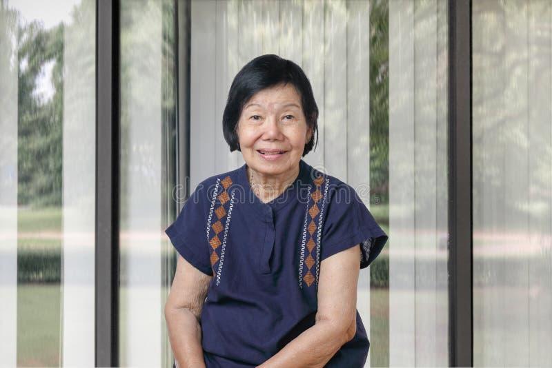 Femme asiatique heureuse détendant dans le salon image libre de droits