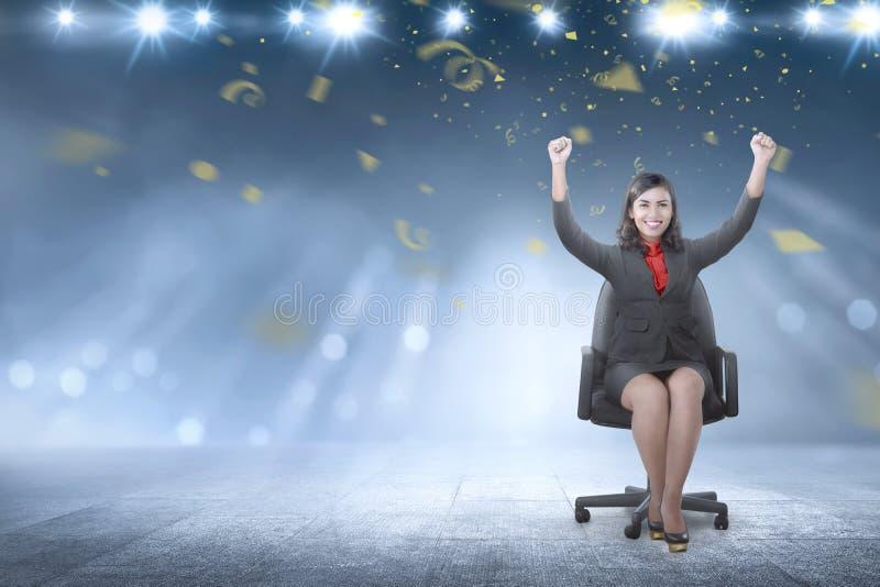 Femme asiatique heureuse d'affaires soulevant ses bras tout en se reposant sur photo stock