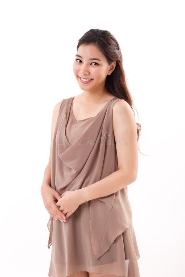 Femme asiatique heureuse et positive dans la robe brune photo libre de droits