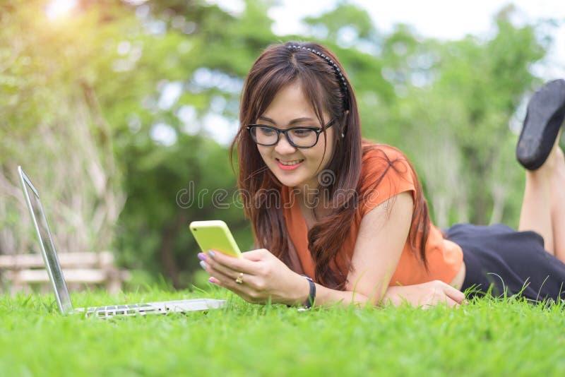 Femme asiatique heureuse ? l'aide du smartphone en d?tendant dans le parc Les gens et le concept de mode de vie Th?me de technolo photographie stock libre de droits