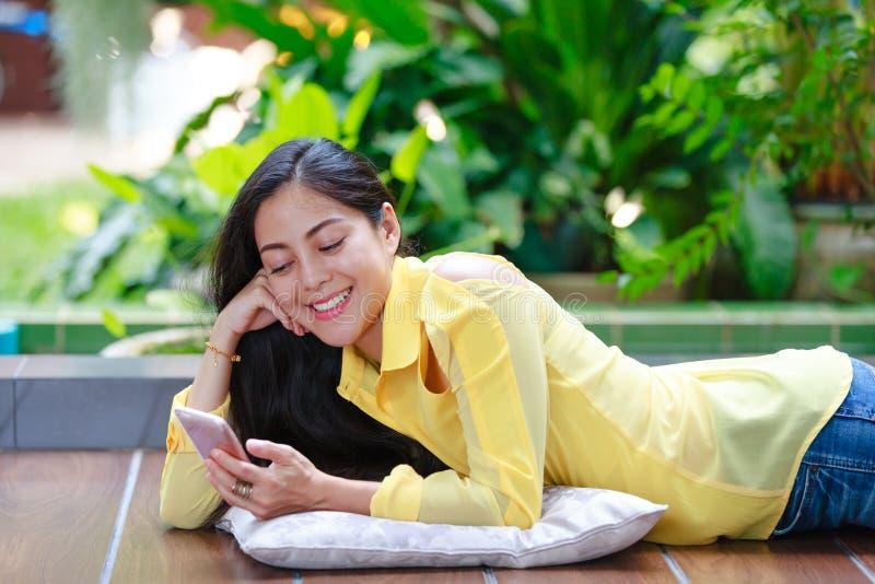Femme asiatique heureuse souriant et à l'aide du téléphone intelligent Dehors sur la somme image stock