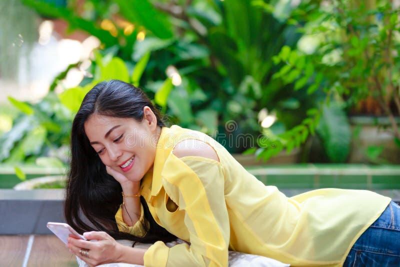 Femme asiatique heureuse souriant et à l'aide du téléphone intelligent Dehors sur la somme images libres de droits
