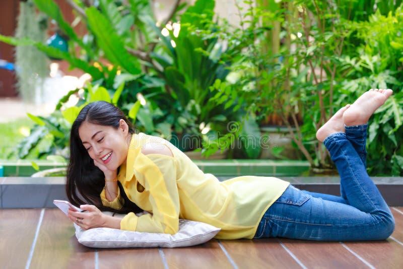 Femme asiatique heureuse souriant et à l'aide du téléphone intelligent Dehors sur la somme photos stock