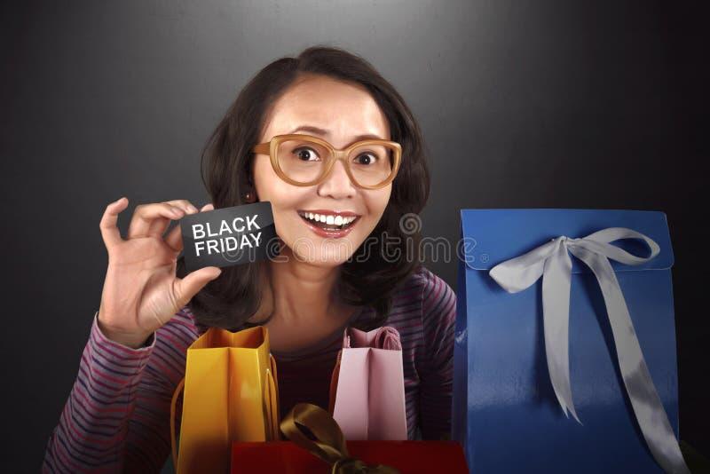 Femme asiatique heureuse tenant la carte avec le texte de Black Friday image stock