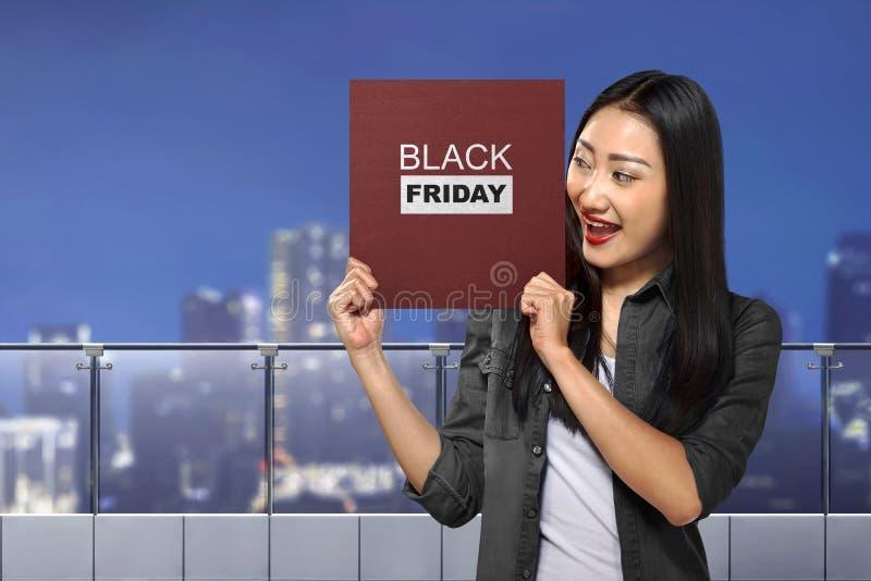 Femme asiatique heureuse tenant le conseil avec le message de Black Friday image libre de droits