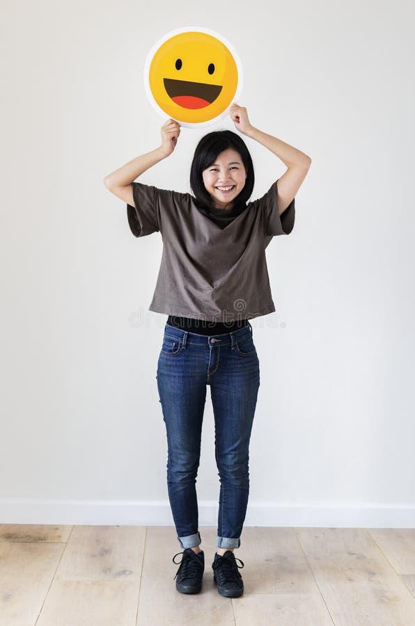Femme asiatique heureuse tenant un visage souriant d'émoticône image stock