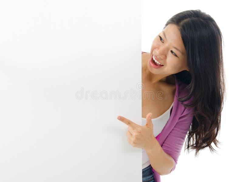 Femme asiatique indiquant le panneau d'affichage vide. photos stock