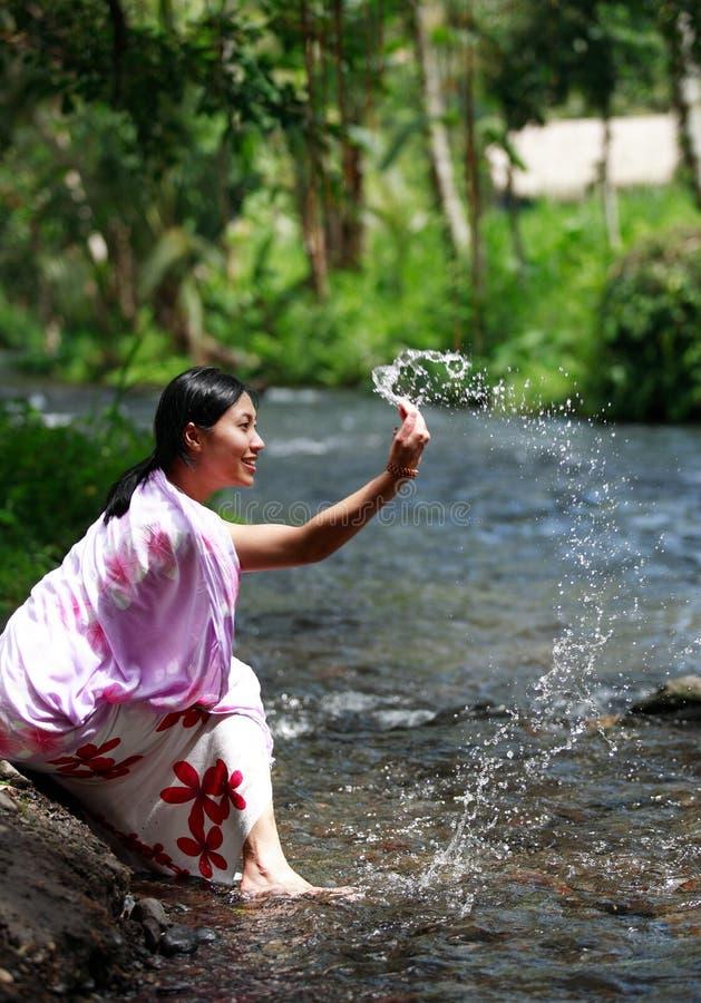 Femme asiatique jouant avec de l'eau photographie stock libre de droits
