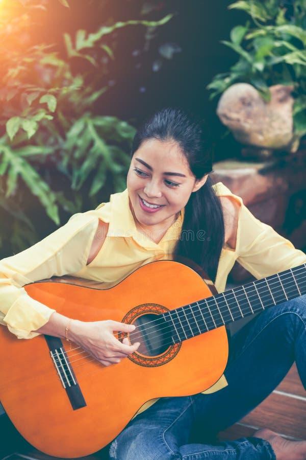 Femme asiatique jouant la guitare acoustique avec la lumière du soleil lumineuse Vinta photographie stock libre de droits