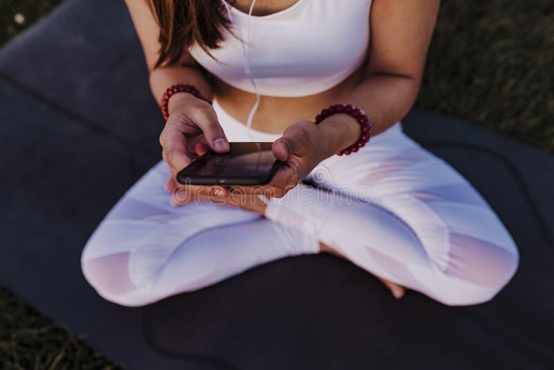 femme asiatique méconnaissable détendue après sa pratique en matière de yoga écoutant la musique aux écouteurs et au téléphone po photos libres de droits