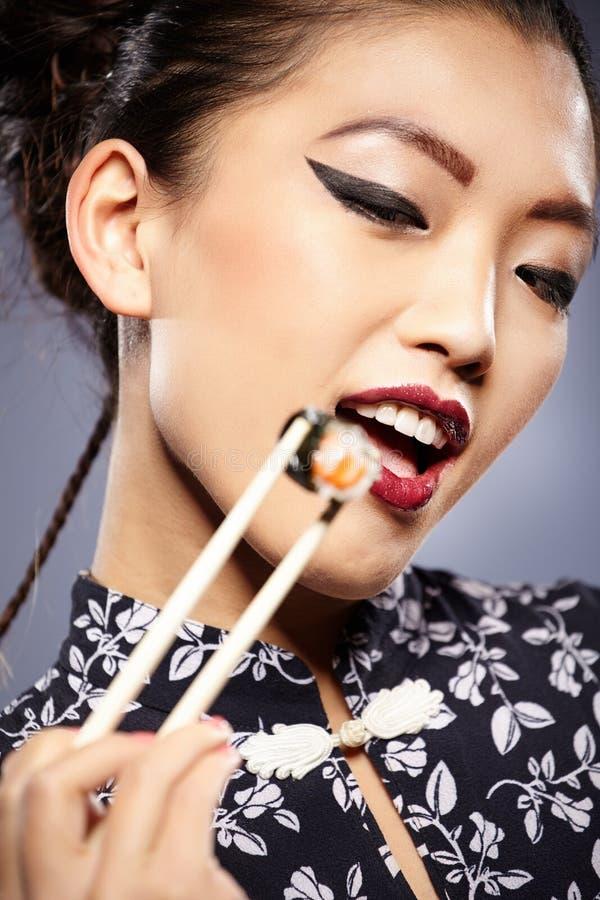 femme asiatique mangeant des sushi, images libres de droits