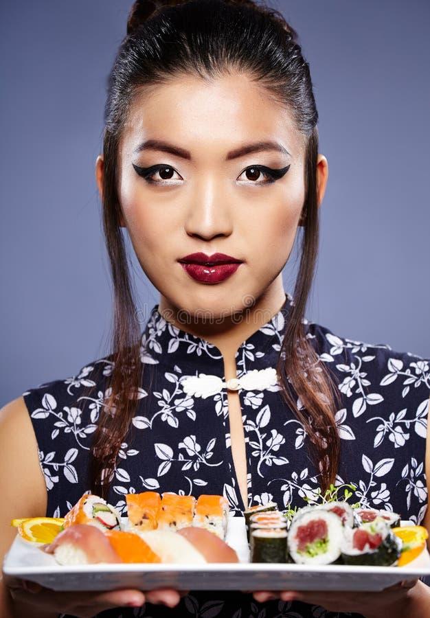 Femme asiatique mangeant des sushi, photographie stock