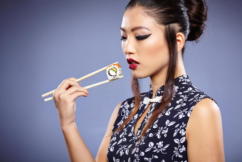 Femme asiatique mangeant des sushi, photo libre de droits