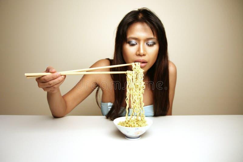 Femme asiatique mignon mangeant des nouilles photographie stock libre de droits