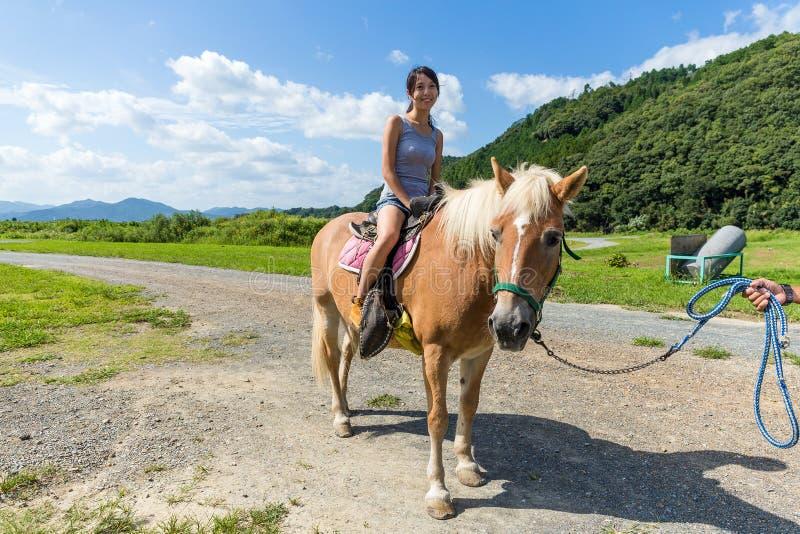 Femme asiatique montant un cheval image libre de droits