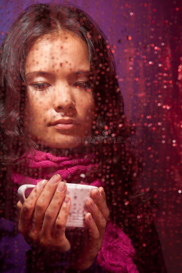 Femme asiatique pensif par temps pluvieux image stock
