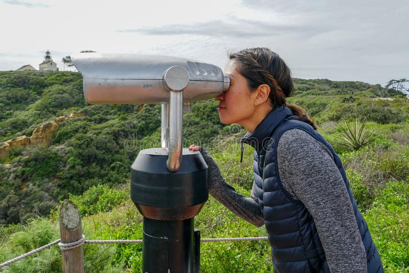 Femme asiatique regardant dans le télescope binoculaire sur l'astuce du point Loma Peninsula à San Diego photos stock