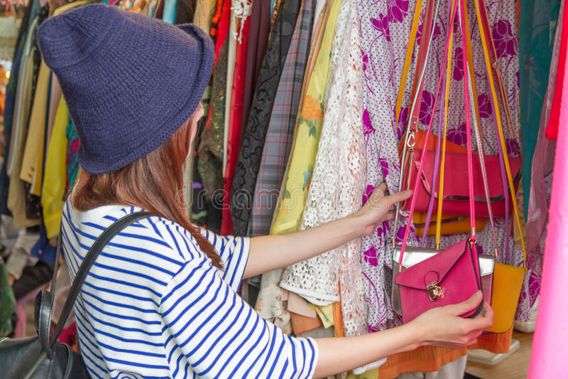 Femme asiatique regardant des sacs sur le support images stock