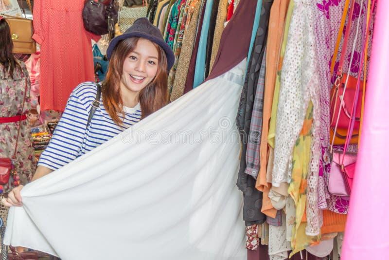 Femme asiatique regardant des vêtements sur le support image stock