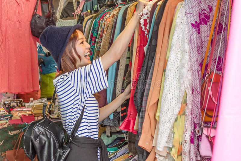 Femme asiatique regardant des vêtements sur le support photo stock