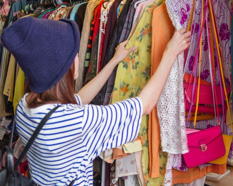 Femme asiatique regardant des vêtements sur le support photographie stock libre de droits